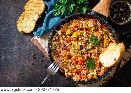 Turkish Cuisine. Menemen Scrambled Eggs In A Cast Iron Frying Pan On A Stone Countertop. Top View Fl