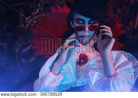 Portrait of a traditional vampire aristocrat of the 19th century in an elegant suit and with a drop of blood on his lips. Halloween.
