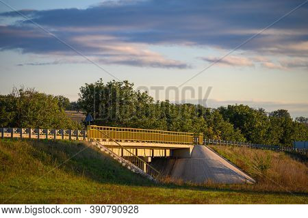 Simple usual road bridge in warm yellow sunset rays
