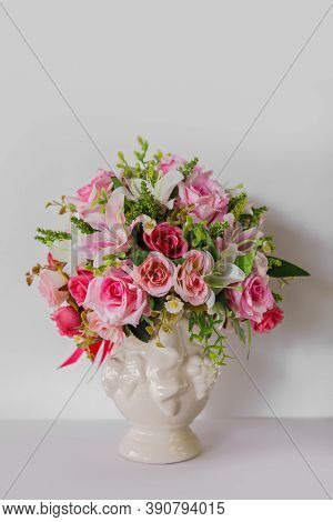 Bouquet Of Flowers In A Round Small Vase On A White Background