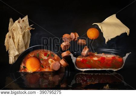 Cutaway vegetable tomato soup with eggs, sausages, melted cheese in levitation and pita on dark background