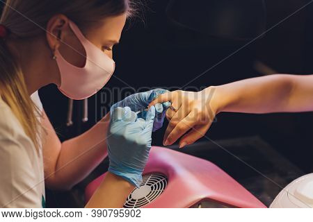 Close-up Of Beautician Applying Colorful Varnish. Applying Nail Polish On Nails With A Brush For App