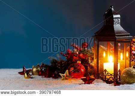 Christmas background with burning candle inside lantern and bauble decorations in snow