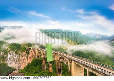 Morning Fog Over Djurdjevica Bridge On River Tara In Mountains Of Montenegro
