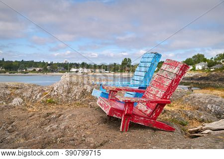 Red And Blue Chairs Victoria. Rustic, Weather Worn Chairs On The Rocky Beach Near Victoria, Bc.