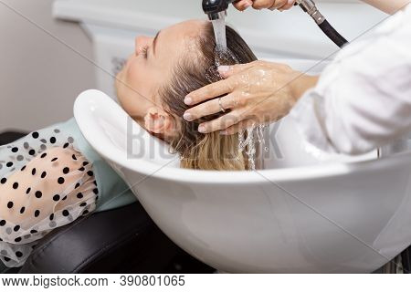 Hair Stylist Washing Hair Of Yong Blonde Young Woman In Hair Salon Before Haircut