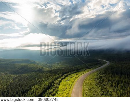 Beautiful View Of Scenic Road From Above Surrounded By Lush Forest, Clouds And Mountains. Aerial Dro