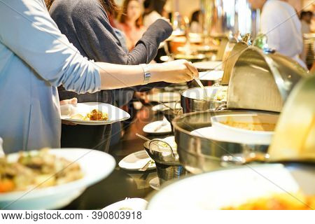Group Of People Grab Some Buffet Self Service Food On Their Own Plate