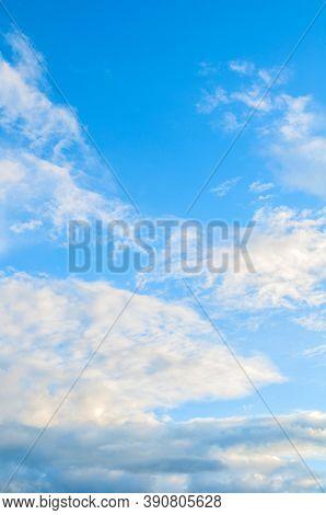 Blue sky background, white dramatic fluffy clouds lit by sunset light. Vast sky landscape scene, blue sky view. Blue sky background, vast sky landscape, sky scene with dramatic clouds.
