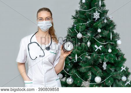 A Female Doctor In A Protective Medical Mask Holds An Alarm Clock On The Background Of A Christmas T