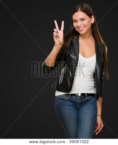 Pretty Young Woman Giving Victory Sign against a black background