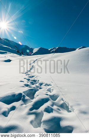 Footprints In The Fresh Snow Mountains Scenery. Beautiful Winter Sunrise. Adventure And Travel Time