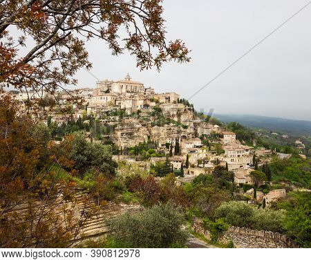 The Ancient Village Of Gordes Resting On The Mountain Landscape In Southern France Framed By Trees.