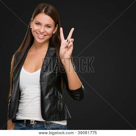 Young Woman Giving Victory Sign against a black background