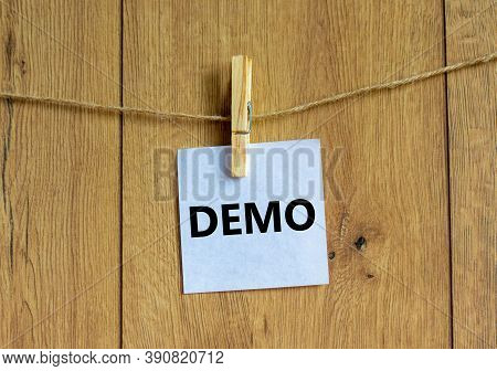 Wooden Clothespin With White Sheet Of Paper. Word 'demo'. Beautiful Wooden Background. Business Conc