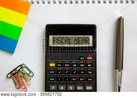 Calculator With Inscription 'fiscal Year', White Note, Colored Paper, Paper Clips, Pen. Business Con