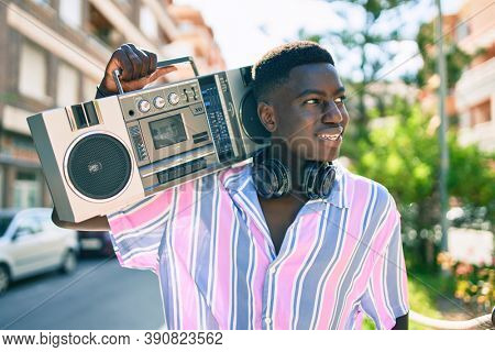 Young african american man listening to music using boom box and headphones walking at street of city.