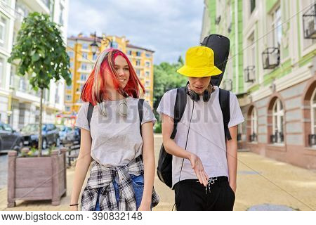 Trendy Teenage Hipsters Boy And Girl Walking Talking On City Street, Boy With Guitar In Case. Youth,
