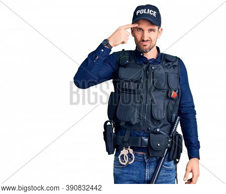Young handsome man wearing police uniform pointing unhappy to pimple on forehead, ugly infection of blackhead. acne and skin problem