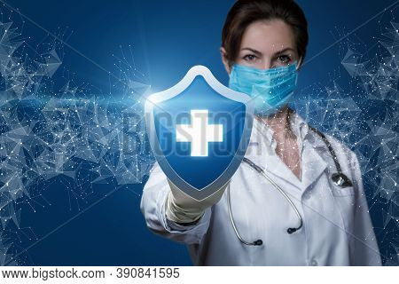 Patient Health Protection Concept. The Doctor Shows A Protecting Shield With A Cross On A Blue Backg