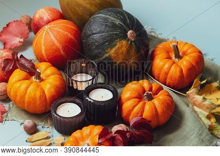 Orange, Green Decorative Pumpkins, Apples, Nuts, Fallen Leaves And Candles In Autumn Harvest Composi