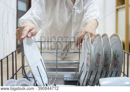 Woman Loading Dishwasher. View From The Inside Of The Dishwashing Machine