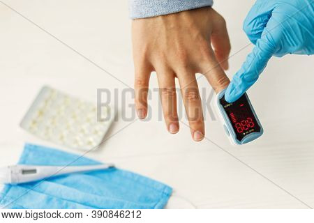 Nurse Measuring Blood Oxygen Level With Portable Pulse Oximeter On  Hand In Clinic Or Home