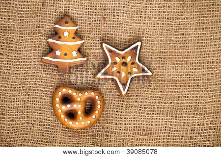Three shapes of ginger bread cake, german lebkuchen on burlap background