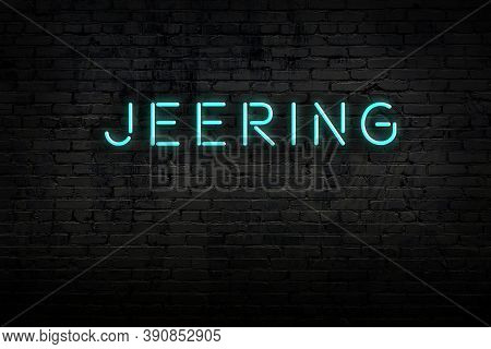 Neon Sign With Inscription Jeering Against Brick Wall. Night View