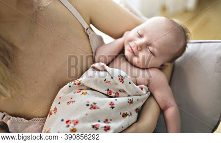 Young Mother Holding Her Newborn Baby Child Sit On A Chair In The Living Room. Close View On The Bab