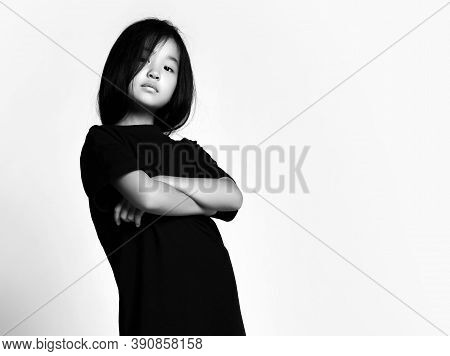 Black And White Portrait Of Self-confident Early Adult Asian Kid Girl In Black T-shirt Dress And Bob