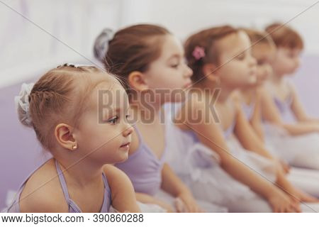 Close Up Of A Beautiful Little Ballerina Girl Sitting With Her Classmates At Ballet School. Group Of