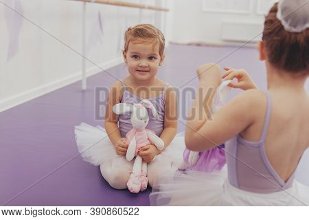Cute Happy Little Girl In Leotard And Tutu Holding Her Toy, Sitting With Her Best Friend At Ballet S