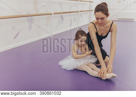 Cute Little Girl Wearing Tut And Leotard, Exercising With Her Teacher At Ballet School. Lovely Young