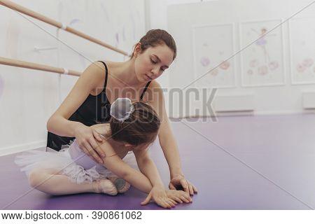 Beautiful Young Ballerina Teaching Little Girl At Ballet School. Adorable Little Girl Wearing Leotar