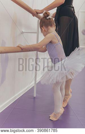 Vertical Shot Of An Adorable Little Ballerina Exercising At Ballet School With Her Teacher. Cute Lit