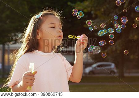 Close Up Of A Lovely Little Asian Girl Blowing Bubbles In The Park, Copy Space. Adorable Little Girl
