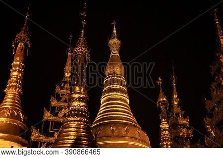 Yangon, Myanmar - December 30, 2019: The Top Of Several Shiny Golden Pagodas Against The Dark Night