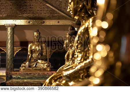 Yangon, Myanmar - December 30, 2019: A Row Of Shiny Golden Buddha Statues Sitting Indoors At The Shw