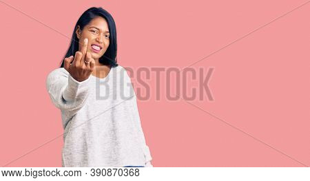 Hispanic woman with long hair wearing casual clothes showing middle finger, impolite and rude fuck off expression