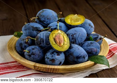 Sweet Plums On A Wooden Plate With Dishcloth On The Brown Table. Selective Focus.