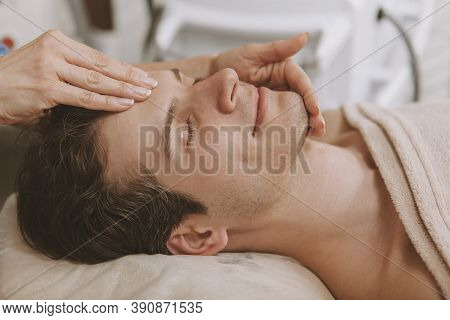 Relaxed Mature Man Smiling With His Eyes Closed, Receiving Head And Face Massage At Spa Center. Chee