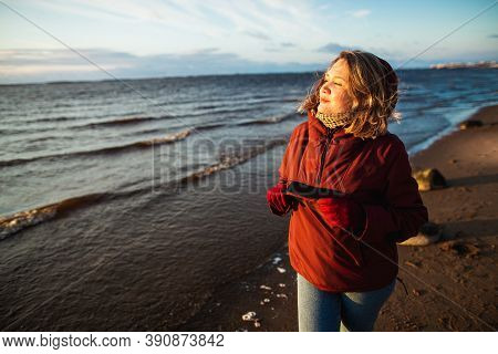 Beautiful Girl With Wild Hair Walking Alone On The Sea Coast. Sunny Winter Day On The Beach
