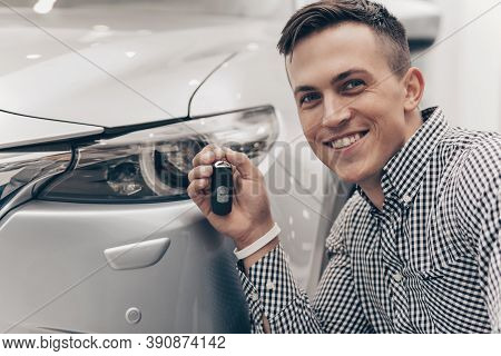 Close Up Of A Happy Young Man Smiling Excitedly, Holding Car Key, Posing With His New Automobile. Ch