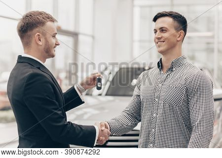 Happy Handsome Man Receiving Car Keys To His New Automobile From Car Salesman At The Dealership. Pro