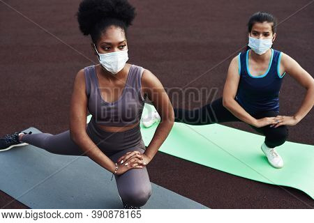 Two Different Ethnic Girls Stretch, Stretch Their Muscles Before Training Outdoors In A Protective M