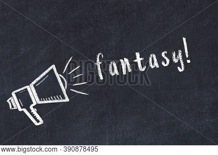 Chalk Drawing Of Loudspeaker And Handwritten Inscription Fantasy On Black Desk