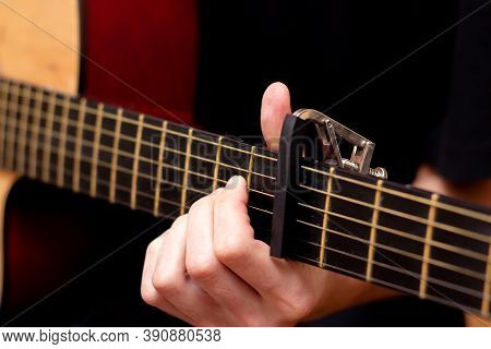 The Guy Plays The Guitar. Capo On The Guitar Fretboard. Close Plan. Wooden Guitar.