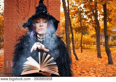 A Witch In A Hat Reads A Spell From A Book. Halloween, A Young Woman At The Carnival In The Guise Of