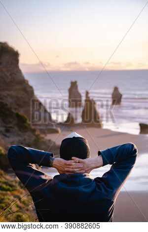 Man With His Hands On Neck Looking At Amazing Scenic Rock Formations By The Beach.